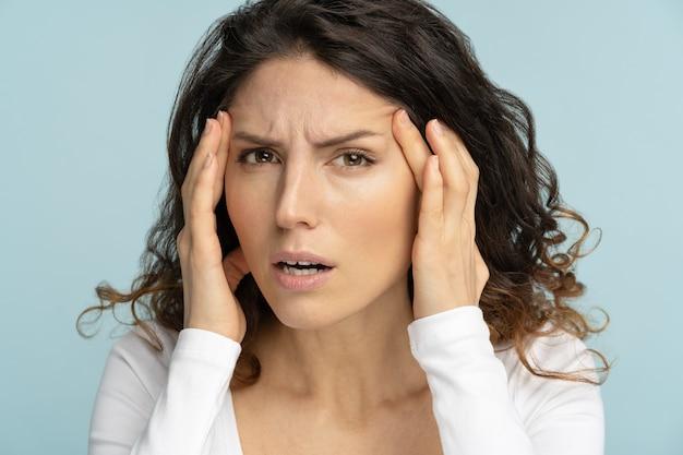 心配している女性は肌の老化の兆候があり、顔のしわに悩まされているカラスの足をチェックし、孤立しています
