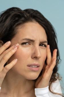心配している女性は肌の老化の兆候があり、顔のしわに悩まされているカラスの足をチェックしています