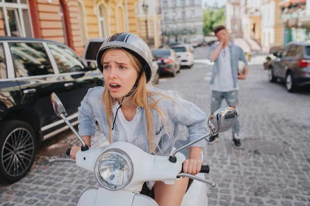 Worried woman is sitting in motorcycle and looking forward