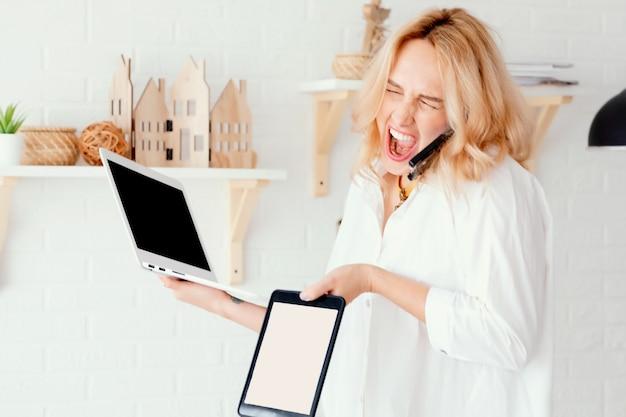 ノートパソコンを持ってオフィスに座って、孤立したプロジェクトに取り組んでいる間、無力なジェスチャーをしている心配している女性