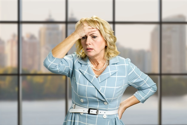 Worried woman on office. stressed busineswoman with headache, migraine or forgetfulness on office window.