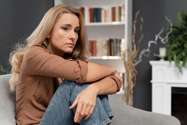 Worried woman sitting in couch