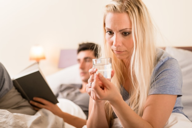 Worried woman taking a pill before sleep at night