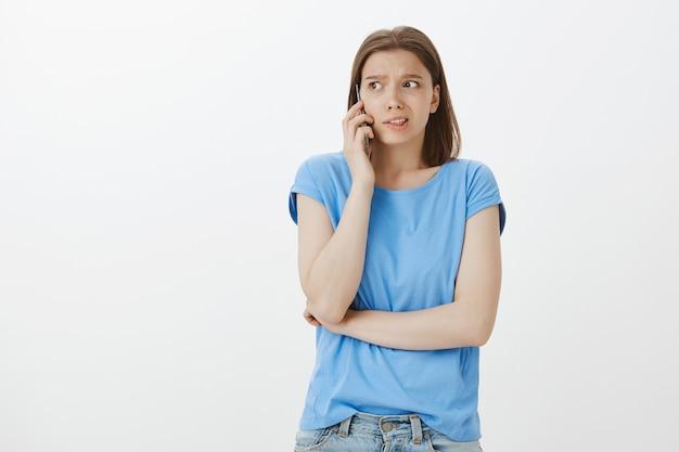 Donna preoccupata che parla al telefono con la faccia interessata, chiedendo aiuto