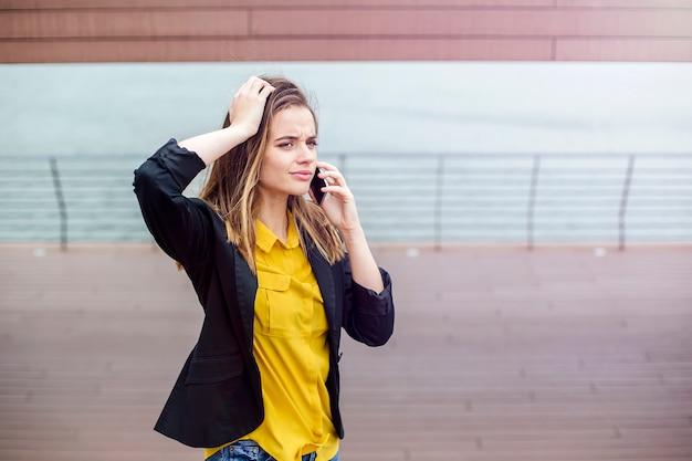 Взволнованная женщина разговаривает по телефону, гуляя по улице