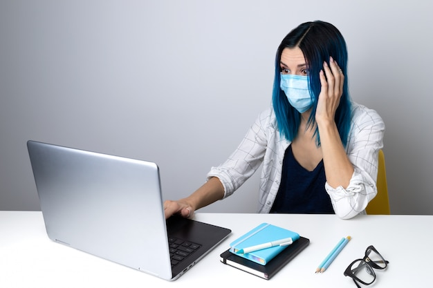 보호 마스크에 파란 머리를 가진 걱정 된 여자는 본사에 앉아 노트북 내용을보고
