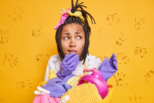 Worried woman with dirty face does cleaning at home looks nervously away stands near laundry basket uses chemical detergents for washing isolated over yellow wall