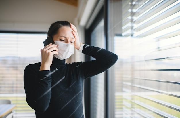 電話とフェイスマスクを自宅の屋内で心配している女性、コロナウイルスと検疫の概念。