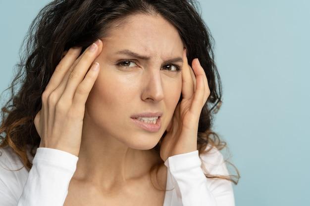 化粧をしていない心配している女性は、肌の老化の兆候があり、顔のしわに悩まされているカラスの足をチェックしています