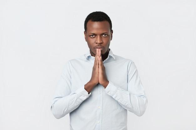 Взволнованный молодой афроамериканец человек, сложив руки, попросить помощи прощения в молитве
