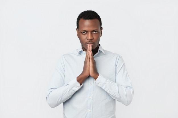 Worried young african american man put hands together ask for help forgiveness in prayer