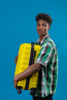 Worried young african american traveler man holding suitcase