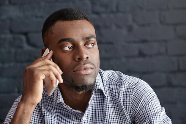 Обеспокоенный молодой африканский бизнесмен разговаривает по мобильному телефону