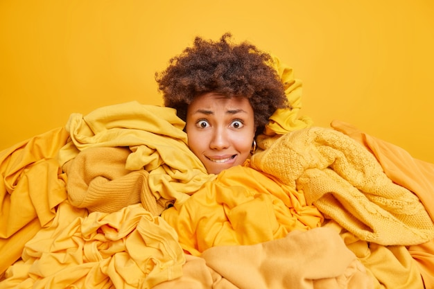 Worried young afro american woman bites lips surrounded by yellow clothes collects items from wardrobe for recycling sticks head through garments takes everything out