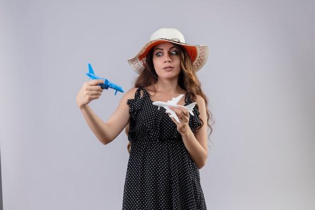 白い背景の上に立ってそれらで遊んでおもちゃの飛行機を保持している夏帽子の水玉のドレスで心配している美しい少女