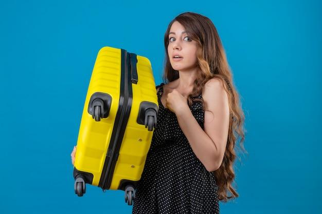 青い背景の上に立っているカメラを見て緊張し、非常に気になるスーツケースを持って心配している若い美しい旅行者の女の子