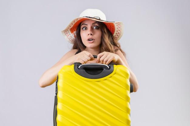Взволнованная молодая красивая девушка путешественника в платье в горошек в летней шляпе держит чемодан, глядя в камеру, стоящую на белом фоне
