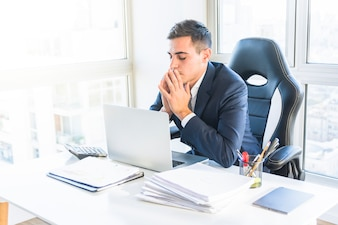 Worried young businessman looking at laptop in the office