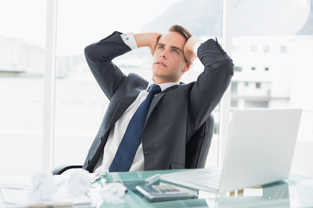 Worried young businessman at office desk