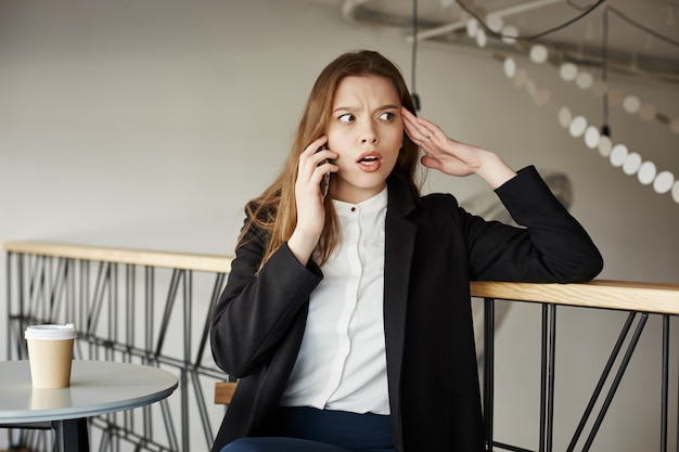 Worried young businesswoman at cafe talking by phone