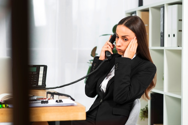 Worried young businesswoman sitting near the wooden desk listening on telephone