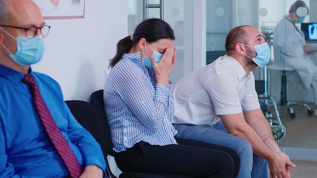 医者からのニュースを待っている間、コロナウイルスの感染に対してフェイスマスクを身に着けている心配している若いカップル。 covid-19の間に不利なニュースから泣いている妻。