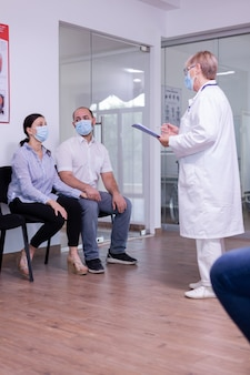 Worried young couple wearing face mask against waiting news from doctor