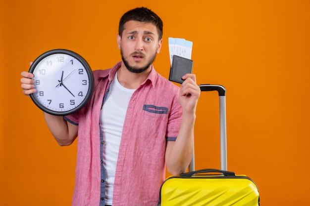 Взволнованный молодой красивый путешественник, держащий авиабилеты и часы, смотрит в камеру с растерянным выражением лица, стоя с чемоданом на оранжевом фоне
