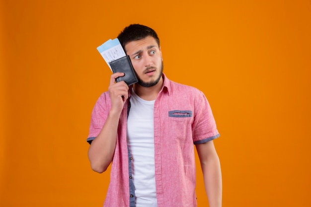 Worried young handsome traveler guy holding air tickets looking aside with fear expression on face standing over orange background