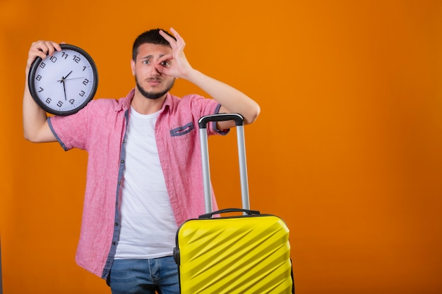 Worried young handsome traveler guy holding clock standing with suitcase doing ok sign and looking through this sign with sad expression on face over orange background