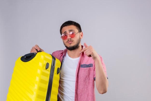 Взволнованный молодой красивый путешественник в солнцезащитных очках смотрит в камеру с растерянным выражением лица, указывая пальцем на свой чемодан, стоящий на белом фоне