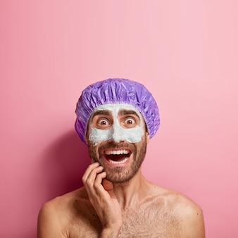 心配している若い男は顔に白い泥マスクを適用し、リフレッシュと若返りを感じ、バスキャップを着用し、ピンクの壁に上半身裸で立っています