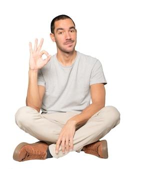 Обеспокоенный молодой человек сомневается и делает жест одобрения