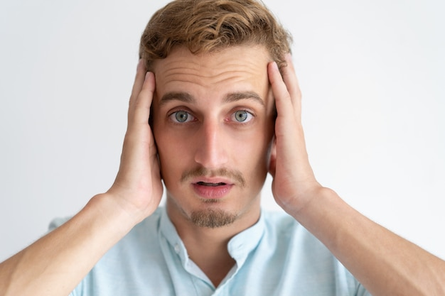 Worried young man looking at camera and touching head