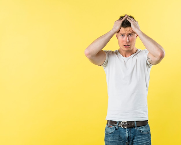 Worried young man with his hand on head standing against yellow background