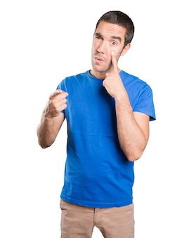 Worried young man with search gesture against white background