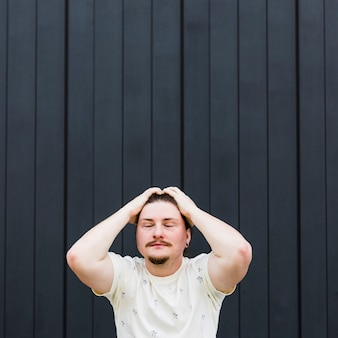 Worried young man with their hands on head against black striped backdrop