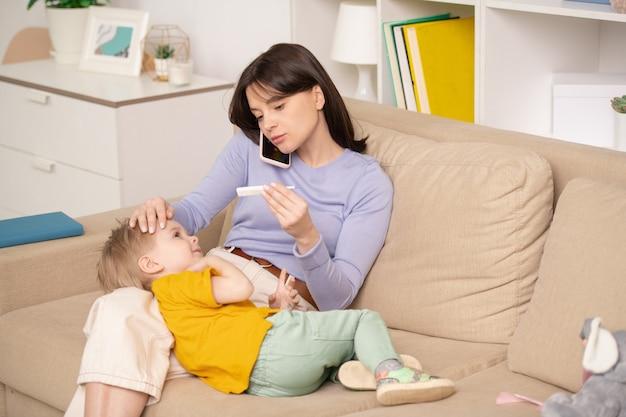 Обеспокоенная молодая мать сидит на диване и проверяет температуру сына, звоня врачу по телефону