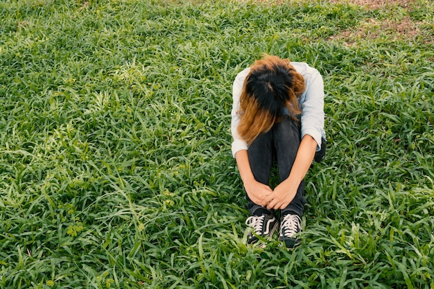 Worried young woman sitting on the grass