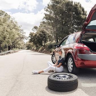 空の道に壊れた車の近くに座っている心配している若い女性