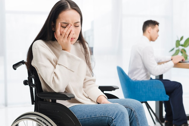 Worried young woman sitting on wheel chair sitting in front of male colleague using laptop