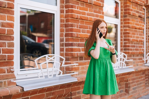 Worried young woman talking on mobile phone standing on city street in summer day, blurred background, selective focus. sad displeased lady calling on phone outdoors