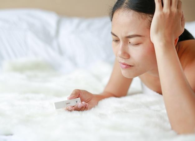 Обеспокоенная молодая женщина с тестом на беременность Premium Фотографии