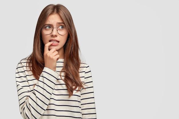 Встревоженная молодая женщина в очках позирует у белой стены
