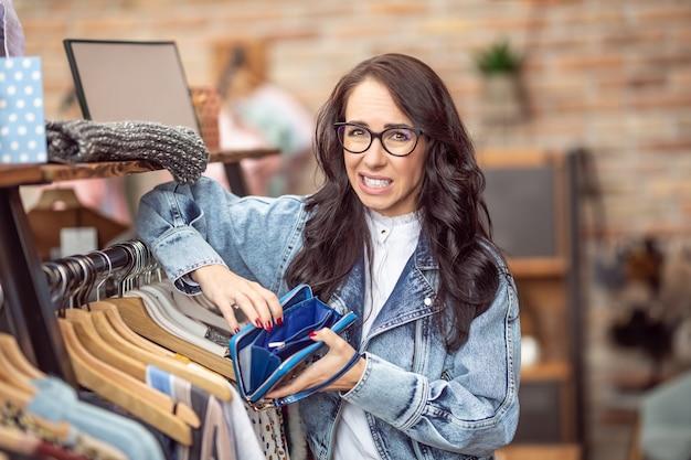 패션 쇼핑을 하는 동안 쇼핑몰에 있는 한 여성이 빈 지갑을 보고 걱정하는 표정.