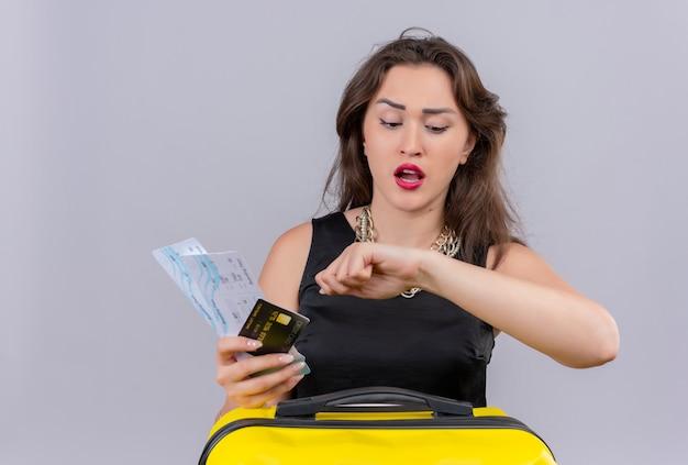 Молодая девушка worrynig путешественника в черной майке держит билеты и банковскую карту на белом фоне
