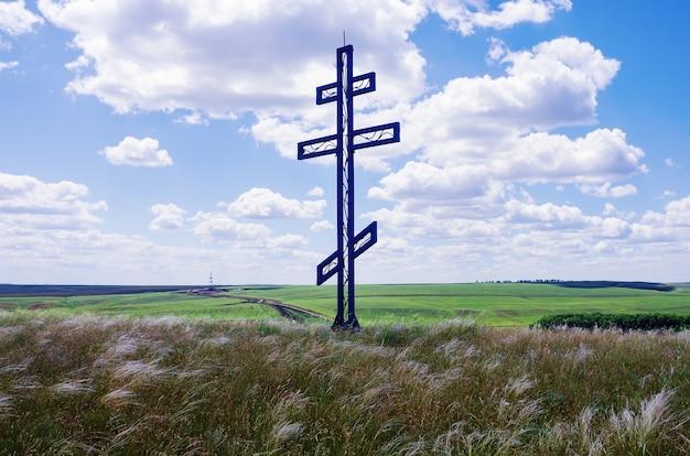 地平線上の草原掘削リグでの崇拝の十字架