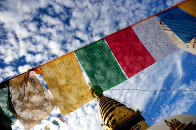 Worship flag under cloudy sky in boudhanath pagoda temple in kathmandu nepal