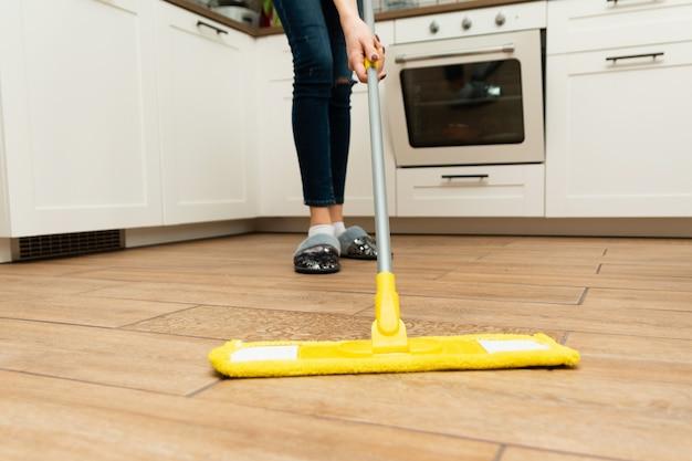 Стоит домохозяйка, уборка пола дома. милая женщина моет деревянные полы из ламината на светлой кухне