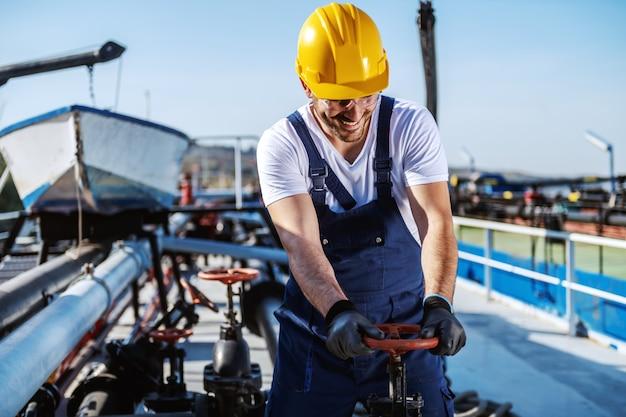 작업 바지에 유조선에 서 고 밸브를 조이는 머리에 헬멧 가치가 백인 웃는 노동자.
